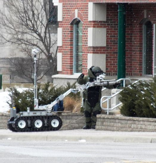 Bomb Team Member in Protective Gear with Robot